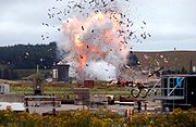 Viewed from a distance, with a telephoto lens, a large explosion is captured in its early stages.  In the foreground, assorted building materials are visible.  In the background, a hillside is partially covered by a forest.