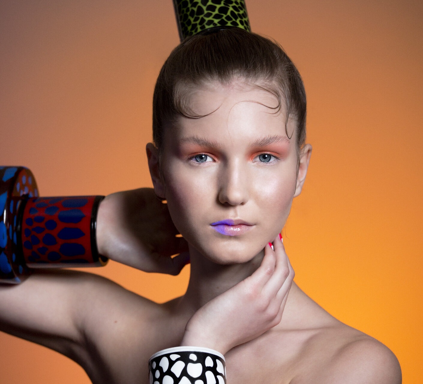 Photo: photographic image photography by Beauty Photographer London Margaret Yescombe, UV lips, Jewellery studio photo-shoot, MUA and hair by Dorota, statement bracelet, stacked bracelets, animal pattern, by Liron Kliger Fashion Jewellery Agency Model, orange lit background