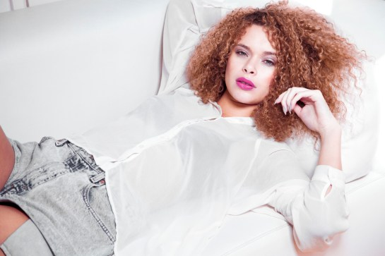 Photo: photographic image by celebrity editorial fashion beauty PR Photographer Hackney London, Model Emerald Oxygen Model Agency, model reclining on couch white sofa, fusha lips, big curls hair long nails