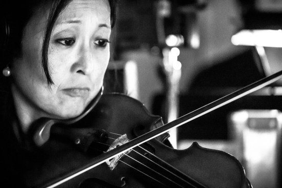 photo: Photography by British Photographer visiting from London Margaret Yescombe, Tony Award Winning Musical, Matilda Orchestra Pit Broadway musician violin player, in the moment, feeling the music