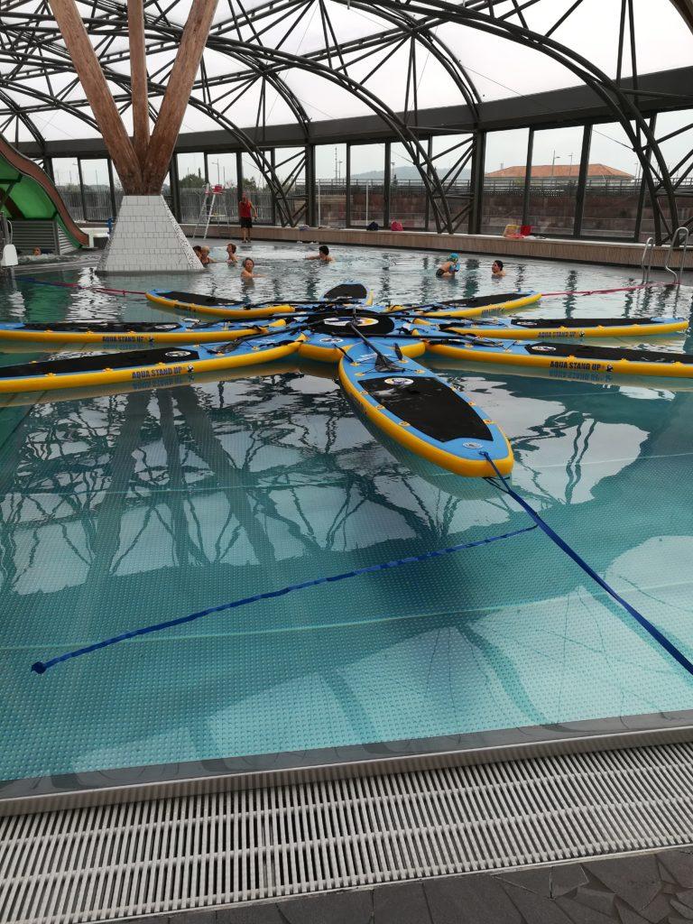 8 planches d'aqua stand up paddle accrochées en rond autour d'une plateforme