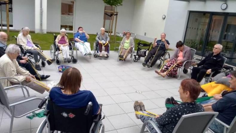 Ein großer Stuhlkreis - gemeinsamer Sport im sitzen im Hof