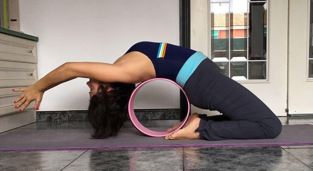 Versión de Vajra Kapotasana con rueda de yoga