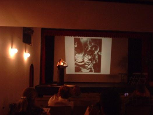 Laescritora y catedráticaespañola, Tina Escaja de la Universidad de Vermont hace una exposición de su trabajo. Ella enseña literatura y viaja por Europa, Estados Unidos y América latina, hablando de la poesía y su visión sobre el estado de la mujer en la sociedad, todo enmarcado en la literatura hipertextual y digital.