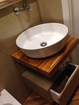 Il piano per il lavandino realizzato con lo stesso parquet e il cassetto rivestito esternamente in resina come la parete