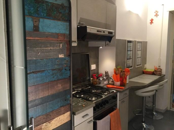 Restyling cucina: zona fuochi dopo. Rivestimento in resina per i mobili, le pareti e il pavimento. Realizzazione di un piccolo piano per la colazione