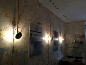 La parete della sala all'entrata con le applique in ottone e gli allestimenti d'arte proposti da StileLibero