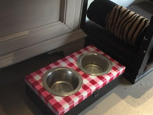 Una scatola in legno trasformata per contenere le ciotoline dell'acqua e della pappa