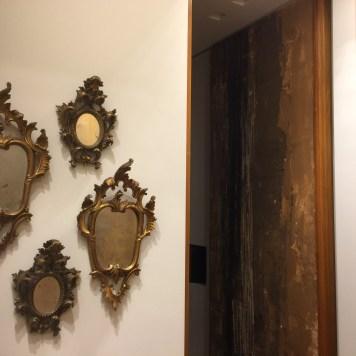Nella parete opposta total white quattro specchi antichi