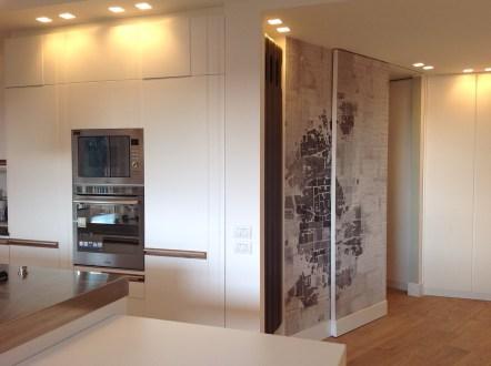 La porta scorrevole che chiude la cucina dall'ingresso rivestita con una carta che rappresenta la pianta di una città.
