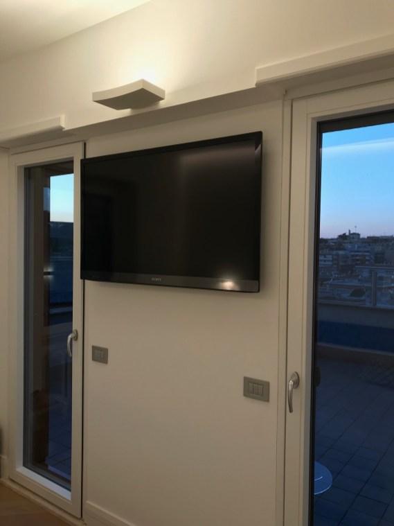 La TV a parete dietro prese e cavi