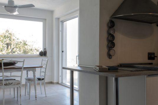 Il top della cucina vicino alla zona fuochi è stato prolungato per creare continuità con la zona pranzo