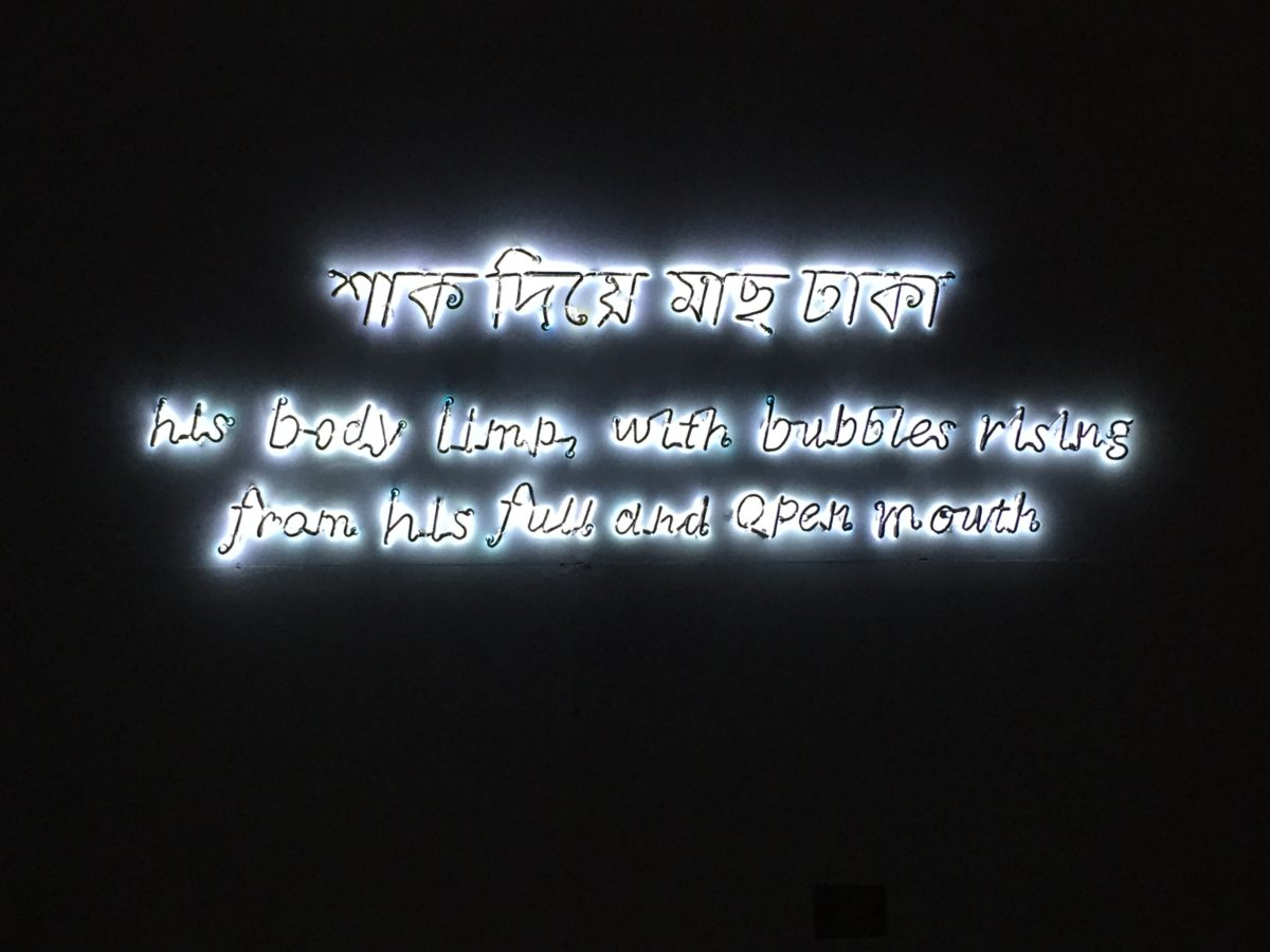 A photograph showing an overpainted neon sign installed in a dark room. The sign reads, in English - his body limp, with bubbles rising, from his full and open mouth, and in Bengali - to cover up a fish with greens.