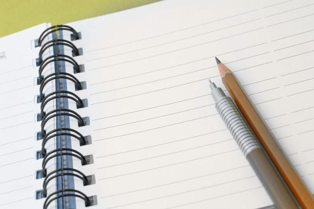 Office stationery ready for use with two pencils lying on a ringbound notebook open at a blank page with lines