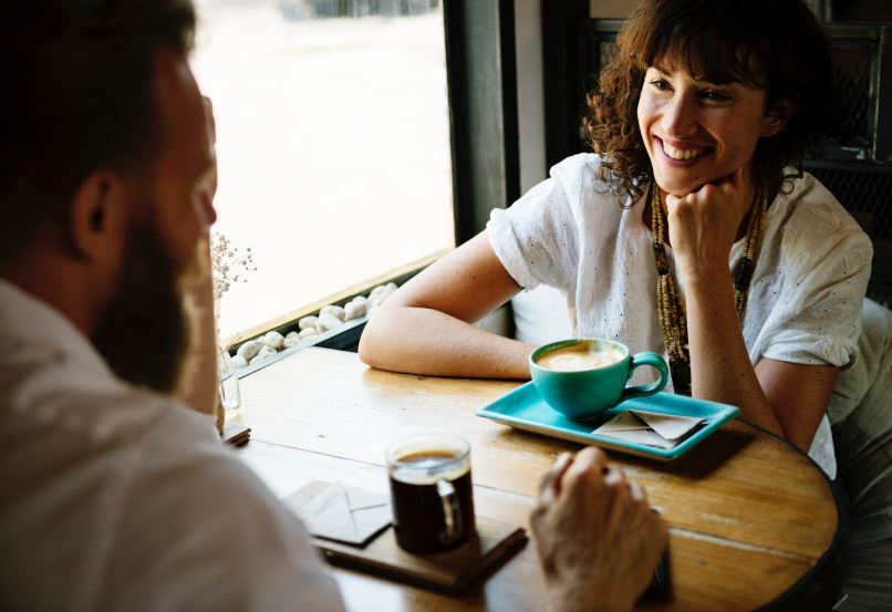 couple talking at a table, Photo by rawpixel on Unsplash