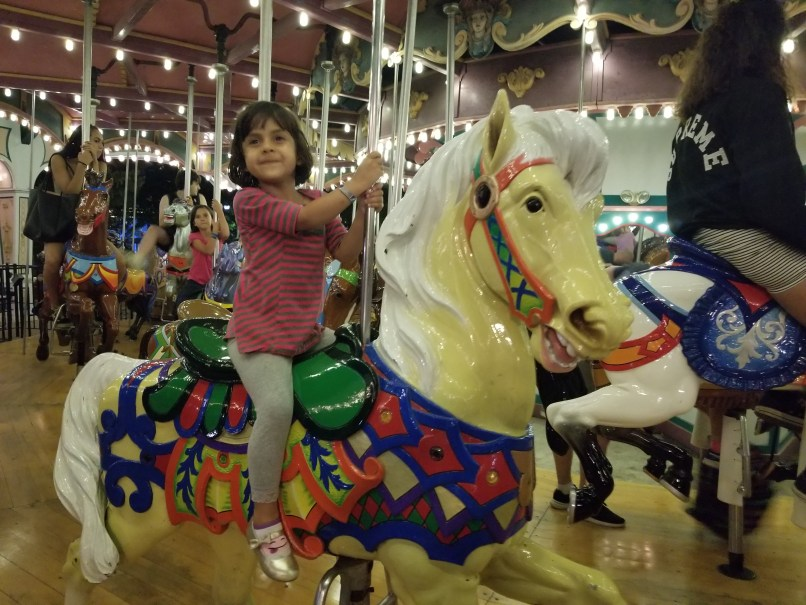 girl riding antique carousel at canada's wonderland