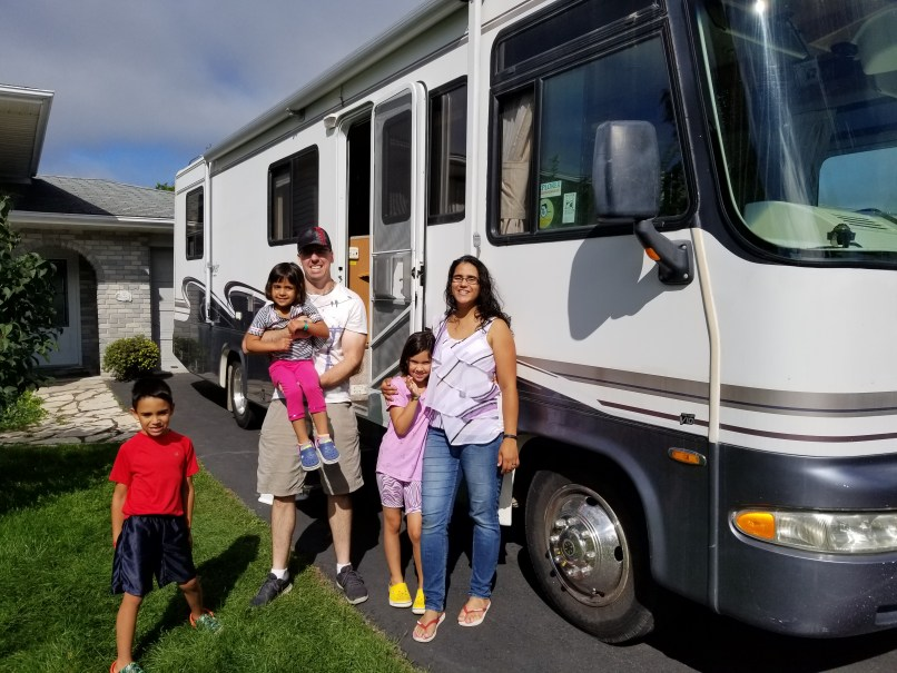 Family in front of RV, long-term travel with kids, rving with kids