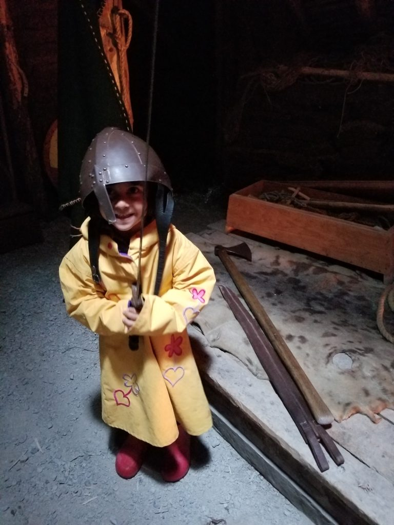 young girl wearing yellow raincoat and a norse helmet, holding a norse sword.