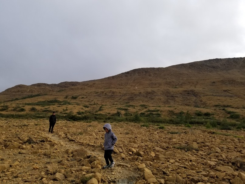 Father and son walking at the base of the tablelands, Gros Morne National Park