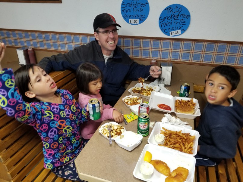 father and three children eating dinner at a small restaurant in Neuvelle, Quebec.