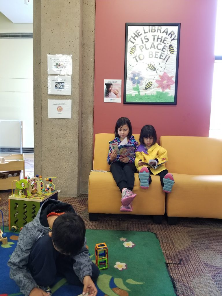 "Two young girls sitting on a yellow coach reading books, while a boy plays with blocks in the foreground. Behind the girls, a sign says ""the library is the place to bee."" Photo taken at the Charlottetown Public Library."