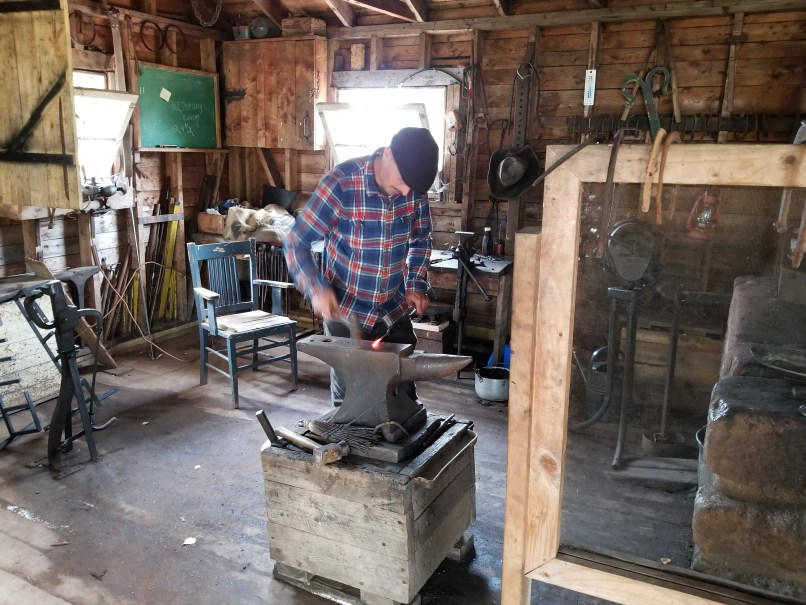 Blacksmith working with a hammer and anvil at Orwell Corner Historic Village, Prince Edward Island. He is wearing a plaid button-up shirt and a black hat.