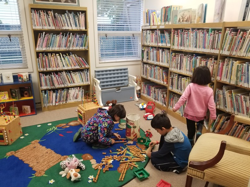 three children playing at a library.