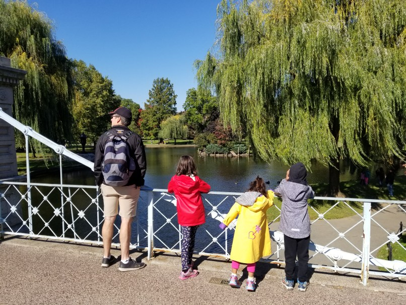 Father and three children looking at weeping willows at Boston Commons