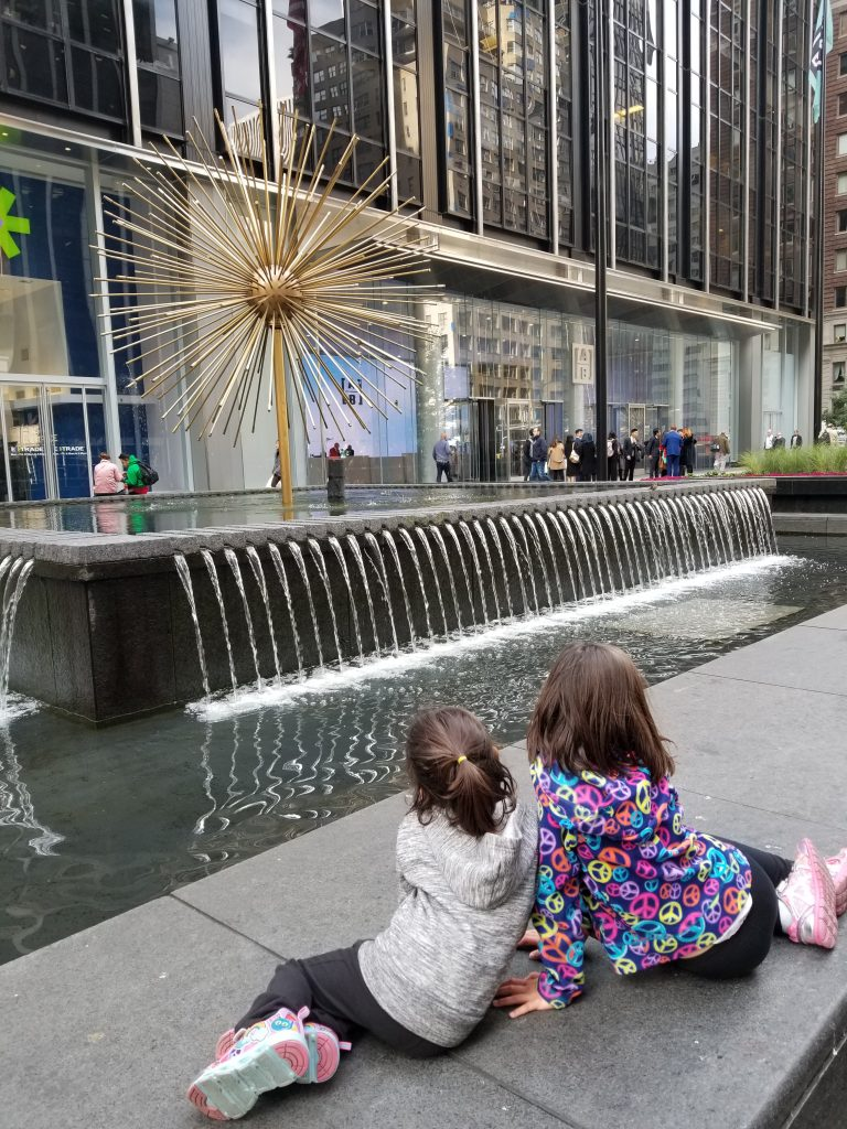 Two young girls look at a sculpture and fountain in front of a building in NYC. They have their backs to the camera.