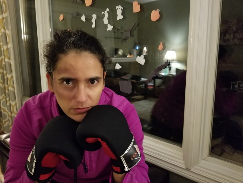 Woman dressed as a boxer for Halloween. She has used makeup to make it look like she has a black eye, and is wearing boxing gloves and a purple sweater. She is sitting in front of a window that is decorated with Halloween stickers.