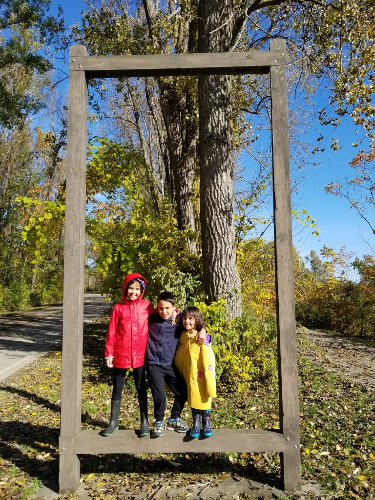 Three children stand inside an empty sign frame at Presque Isle, Erie, Pennsylvannia.