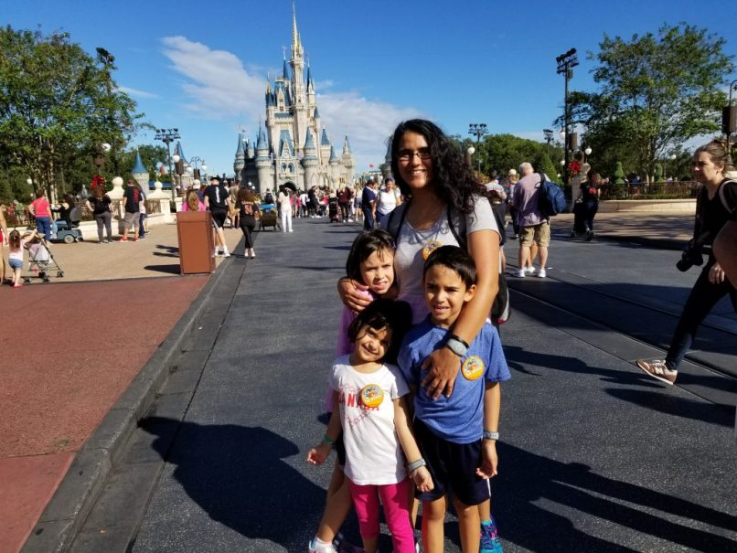Mother with two young daughters and a son, Disney World castle in background.
