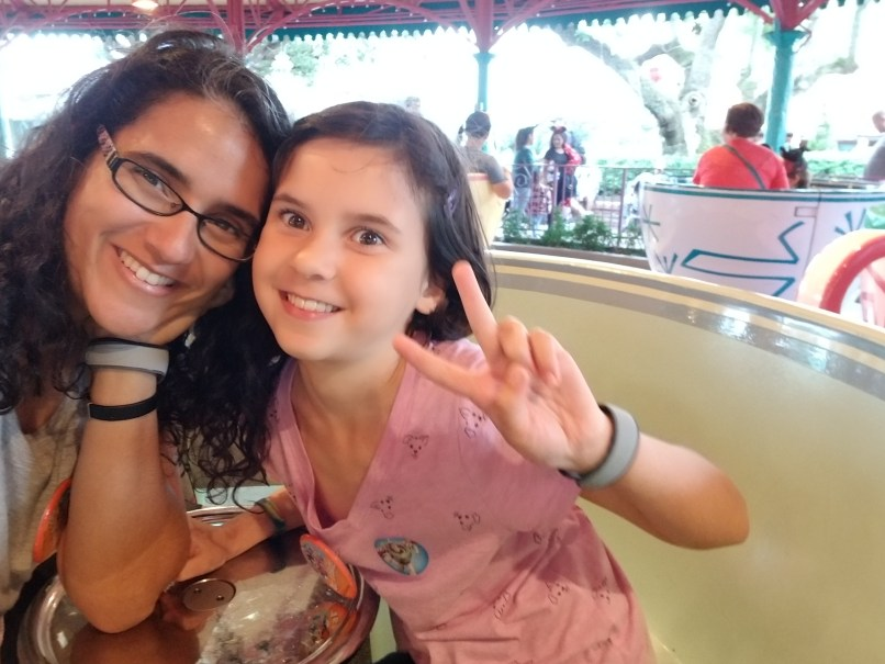 Mother and daughter sitting in a cup at the spinning tea cups ride at Magic Kingdom, Disneyworld. The daughter is making the peace sign.