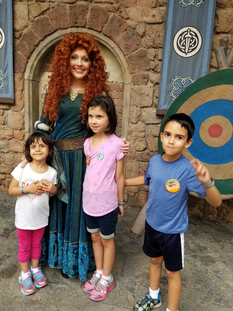 """Actress portraying the Disney character Merida, from the movie """"Brave,"""" poses with two young girls and a young boy at Magic Kingdom in Disney World"""