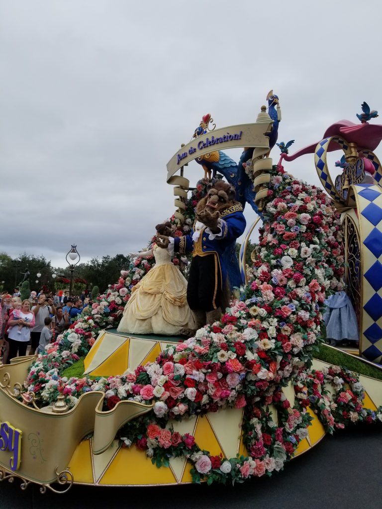 Beauty and the Beast atop a flot decorated with flowers at the Magic Kingdom Parade, Disney World