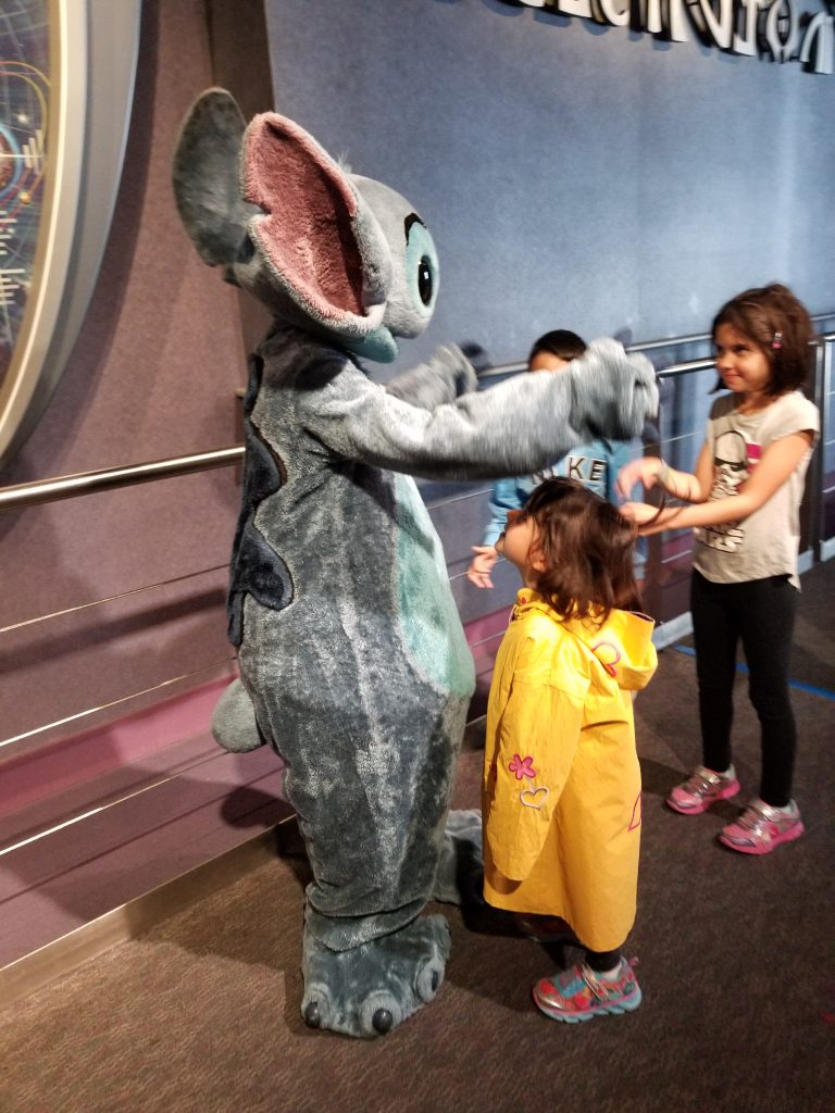 Stitch, from the movie Lilo & Stitch, meets two young girls and a young boy at Magic Kingdom