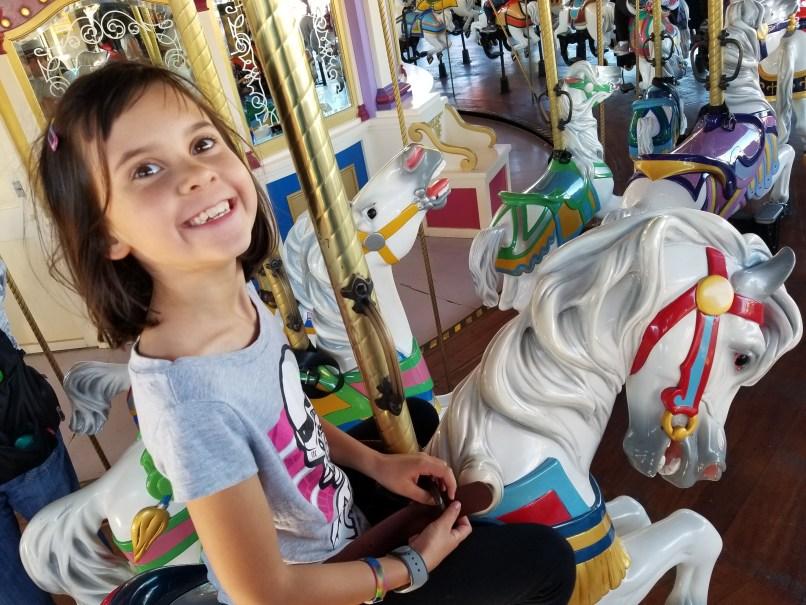 Girl sitting on a carousel horse at Magic Kingdom