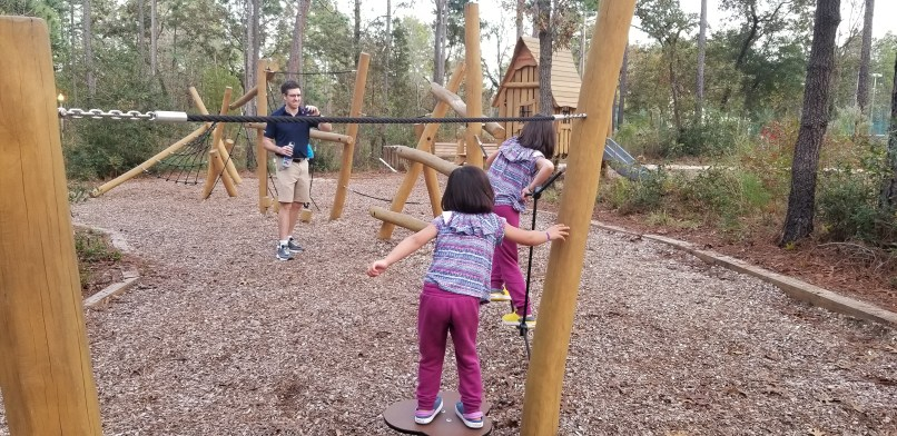 A father observes as three children walk through an obstacle course in an Ocala, Florida playground.