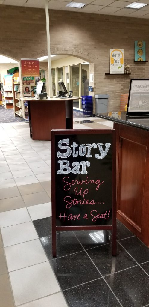 Sign at Sterling Public Library in Baytown, Texas. The sign reads; Story Bar. Serving up stories... have a seat!