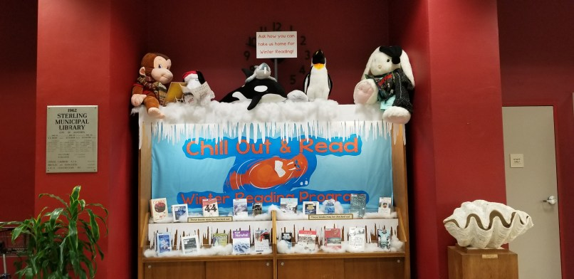 "Winter Reading Program Display at Sterling Public Library in Baytown, Texas. Books, stuffed animals, and a sign that says ""chill out and read."""