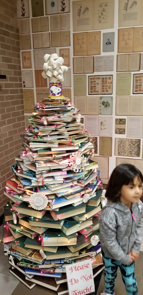 4-year-old girl standing in front of a Christmas tree made out of books at the Sterling Public Library in Baytown, Texas