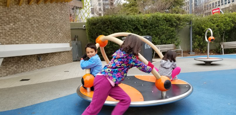 A boy and two girls go around on playground equipment.