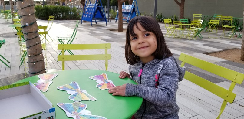 A 4-year-old girl smiles at the camera. She is sitting at a table, showing her just-finished butterfly puzzles.