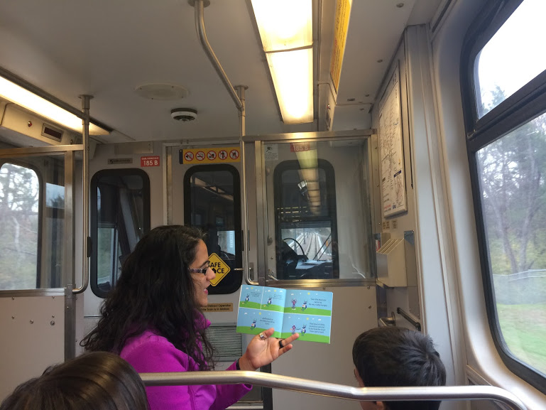 A mother reads a book to her children on the train into Dallas.
