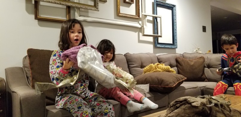 Two girls and a boy opening Christmas presents in an airbnb in Granbury, Texas