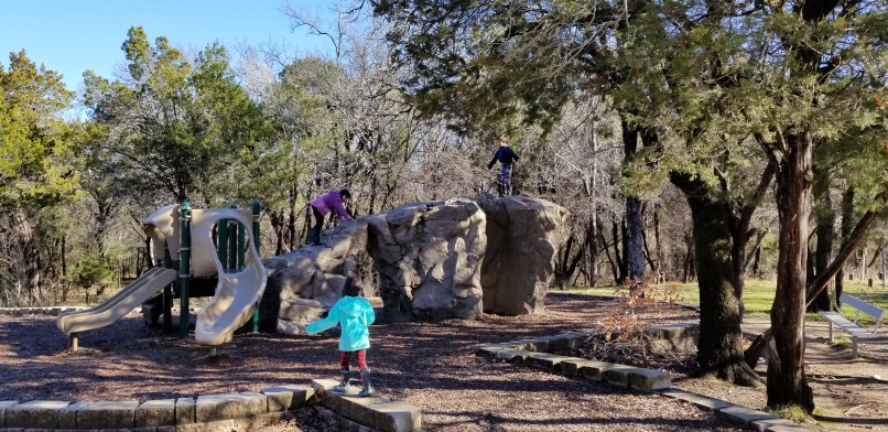 Two girls and a boy playing at a playground in Dinosaur Valley State Park, Texas