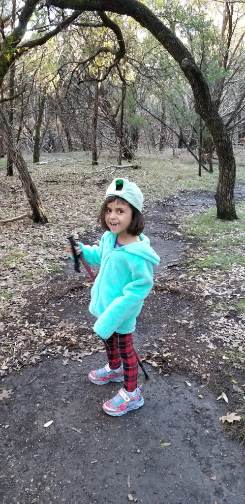 M-girl wearing her baseball cap backwards and holding a hiking stick at Meridian State Park