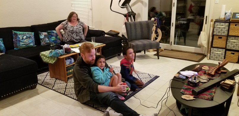 A man is playing a video game while holding a 4-year-old girl on his lap. A boy is sitting beside him, and a woman is sitting on the sofa in the background.
