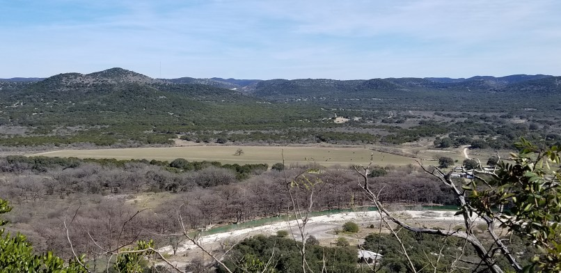 View from Bridges Trail at Garner State Park, Texas. The Frio River, a farm, and some mountains are visible. Photo by Mariana Abeid-McDougall