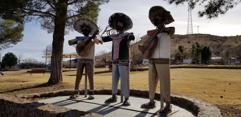 An iron sculpture depicts three mariachi wearing sombreros and playing guitars in Alpine, Texas.